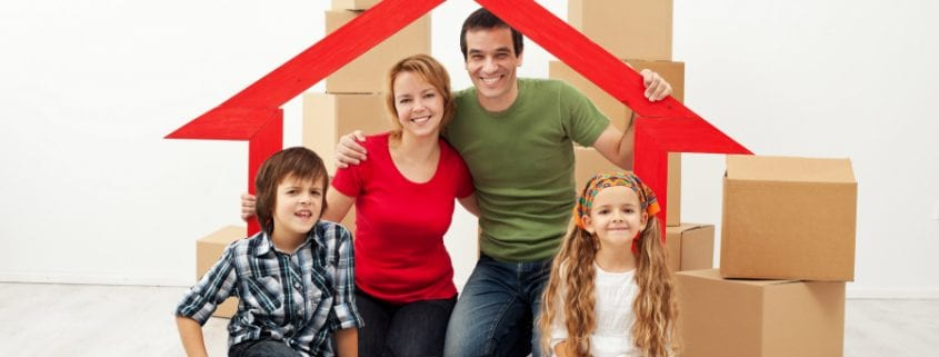 Happy family with boxes behind them moving in Greensboro NC